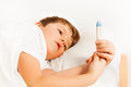 Boy lying in bed and checking thermometer readings Royalty Free Stock Photo