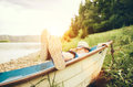 Boy lying in old boat near the lake Royalty Free Stock Photo