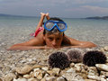 Boy lying in sea with sea urchins Royalty Free Stock Photography