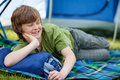 Boy lying on sleeping bag young with tent in background Stock Photography