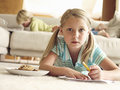 Boy lying on sofa at home focus on girl lying on floor with paper and biscuits surface level Royalty Free Stock Photo