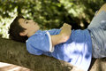 Boy lying on a tree branch Stock Photo