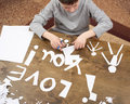 Boy makes origami - car and family, children, parent, I love you text, top view on wood background Royalty Free Stock Photo