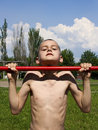 Boy makes sport exercises on the horizontal bar Stock Photos