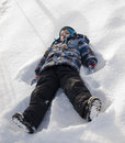A boy making snow angels young makes Royalty Free Stock Image