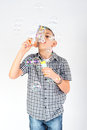 Boy making soap bubbles in studio Stock Photo