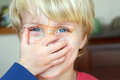 Boy with marker on face cute blonde toddler covering his his hand his is covered in Stock Photos