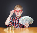 Boy with money portrait of a funny in red framed glasses cash banknotes and coins Royalty Free Stock Image