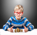 Boy with money portrait of a funny in red framed glasses looking at piles of coins Stock Photos