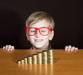 Boy with money portrait of a funny in red framed glasses looking at piles of coins Stock Image