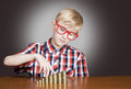Boy with money portrait of a funny in red framed glasses the piles of coins Stock Images