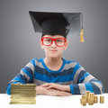 Boy with money preteen in a mortar board piles of coins Stock Image