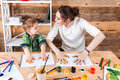 Boy and mother making prints of painted hands on paper Royalty Free Stock Photo