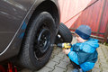 Boy mounted tires on a car. Royalty Free Stock Photo
