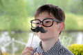 Boy with moustache toy and glasses posing in front of a photo booth Royalty Free Stock Images