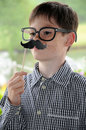 Boy with moustache toy and glasses posing in front of a photo booth Royalty Free Stock Image