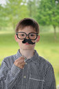Boy with moustache toy and glasses posing in front of a photo booth Royalty Free Stock Photos