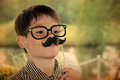Boy with moustache toy and glasses posing in front of a photo booth Stock Photography