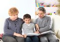 Boy with my grandparents cute sitting in the lap of their and looking happily together at a photo album Royalty Free Stock Photography