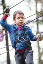 Boy on obstacle in adventure park young with serious expression navigating Stock Photos