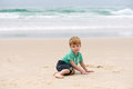 Boy at the ocean cute shy little sitting on sand in front of Stock Image
