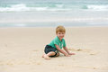 Boy at the ocean cute smiling little sitting on sand in front of Royalty Free Stock Photography
