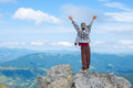 Boy with open arms stands on the cliff Royalty Free Stock Photo