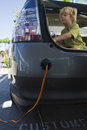 Boy in open car trunk at gas station side view of a sitting Royalty Free Stock Images