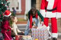Boy opening christmas present in courtyard with children and santa claus Stock Image