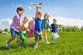 Boy with other kids runs and holds airplane toy Royalty Free Stock Photo