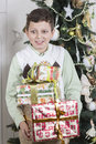 Boy is overwhelmed with many christmas gifts young Stock Photos