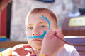 Boy painting face with shark outdoors Stock Image