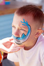 Boy painting face with shark outdoors Royalty Free Stock Photography