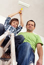 Boy painting the room with his father sitting on old ladder paint roller Stock Image