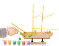 Boy paints model sailing ship Royalty Free Stock Photo