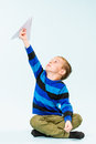 Boy and paper airplane happy playing with in studio light blue background Stock Photos