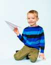 Boy and paper airplane happy playing with in studio light blue background Stock Images