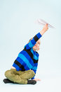 Boy and paper airplane happy playing with in studio light blue background Royalty Free Stock Photo