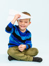 Boy and paper airplane happy playing with in studio light blue background Royalty Free Stock Images