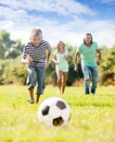 Boy with parents playing with soccer ball teenager at summer park Royalty Free Stock Photography
