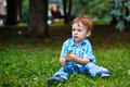Boy in the park little jeans and a plaid shirt sitting on grass Stock Images