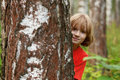 Boy peeking out from behind a tree trunk cheerful Stock Photo