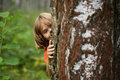 Boy peeking out from behind a tree trunk playful Stock Photos