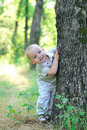 Boy peeks from behind a tree in the forest Stock Photo