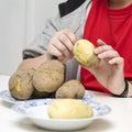 Boy peeling potatoes Stock Photos