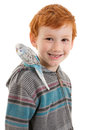 Boy with pet bird budgerigar on shoulder smiling isolated white Stock Images