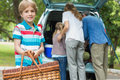Boy with picnic basket while family in background at car trunk portrait of a Royalty Free Stock Photo