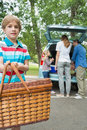 Boy with picnic basket while family in background at car trunk portrait of a Royalty Free Stock Photography