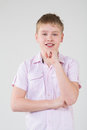 The boy in a pink shirt propping up hand to head studio Stock Photos