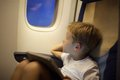Boy in plane looking out illuminator with pad on Royalty Free Stock Photo